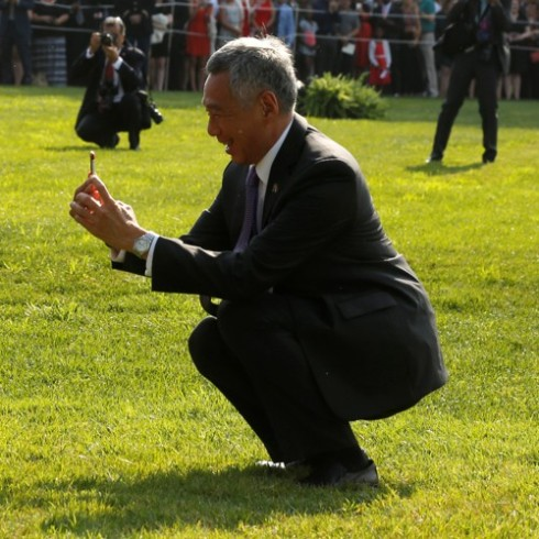 Lee stops to take a picture as he and Obama greet visitors during an official arrival ceremony on the South Lawn of the White House in Washington, U.S.